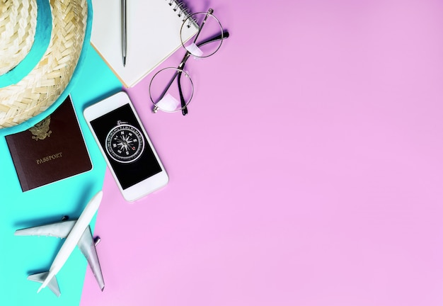 Accessoires de voyage d'été avec boussole sur téléphone sur l'espace de copie rose bleu