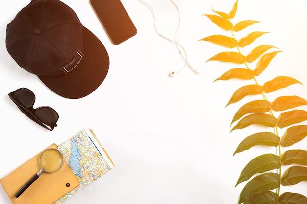 Accessoires de voyage sur fond blanc carte de casquette de casque intelligent et lunettes de soleil point de vue de dessus su...