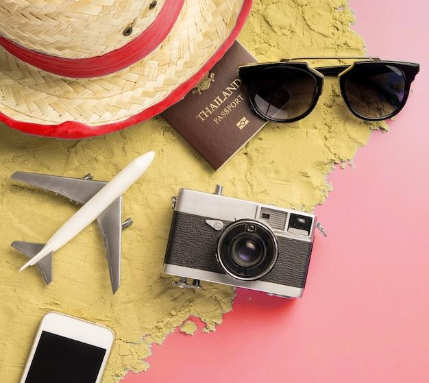 Accessoires de voyage et mode sur sable et rose