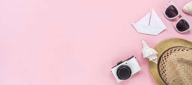 Accessoires de voyage à plat sur fond rose pastel avec petit appareil photo blanc, lunettes de soleil, chapeau de paille. concept de voyage ou de vacances vue de dessus avec espace de copie, bannière