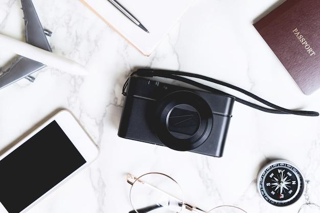 Accessoires de voyage à plat sur marbre avec caméra au centre