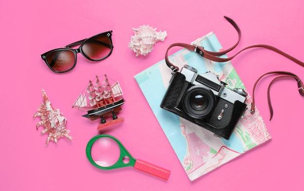 Accessoires de voyageur avec appareil photo rétro sur rose
