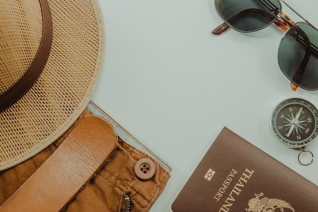 Accessoires de voyageur et costume sur fond blanc avec espace copie, concept de voyage.