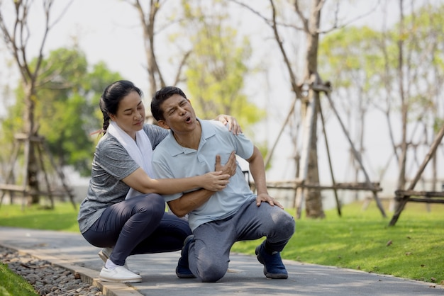 Accident de l'homme âgé ou senior asiatique tombant sur le sol dans le parc lors de l'exercice de course ont mal au genou.