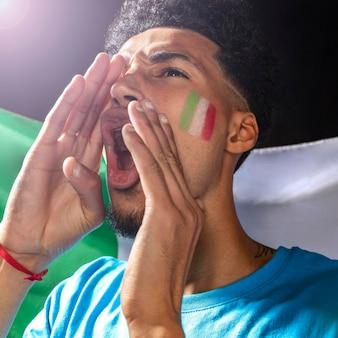 Acclamations de l'homme avec le drapeau italien sur son visage