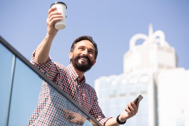 Acclamations. joyeux bel homme, boire du café tout en se tenant à l'extérieur