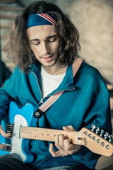 Accompagnement à la guitare. musicien qualifié aux cheveux longs avec du chaume noir chantant et jouant en même temps pendant des moments paisibles