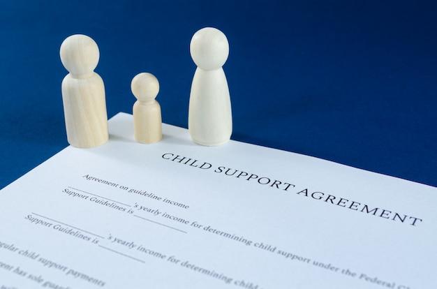 Accord de pension alimentaire pour enfant imprimé avec des figures en bois homme, femme et enfant dans une image conceptuelle pour une pension alimentaire pour enfants sur fond bleu.