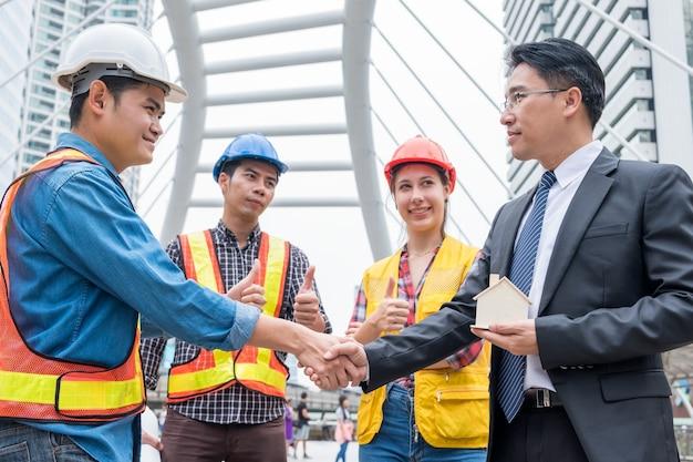 Accord de poignée de main de groupe d'ingénieur avec l'homme d'affaires pour la construction résidentielle de projet
