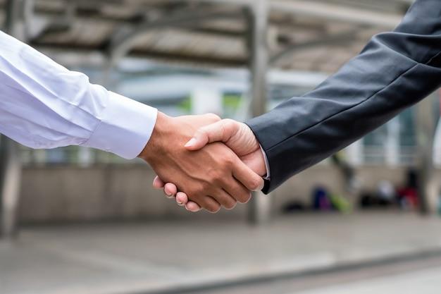 Accord de poignée de main d'un homme d'affaires avec un partenariat dans la ville