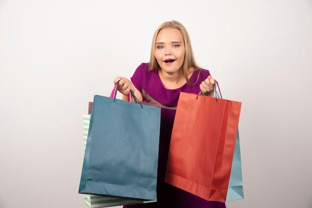 Accro du shopping blonde tenant des sacs à provisions colorés.