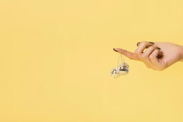 Accrocher des boules de noël tenues à la main avec espace de copie