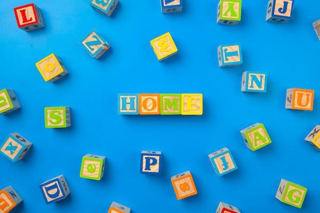 Accueil. blocs d'alphabet coloré en bois sur bleu