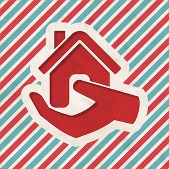 Accueil dans l'icône de la main sur fond rayé rouge et bleu. concept vintage au design plat.