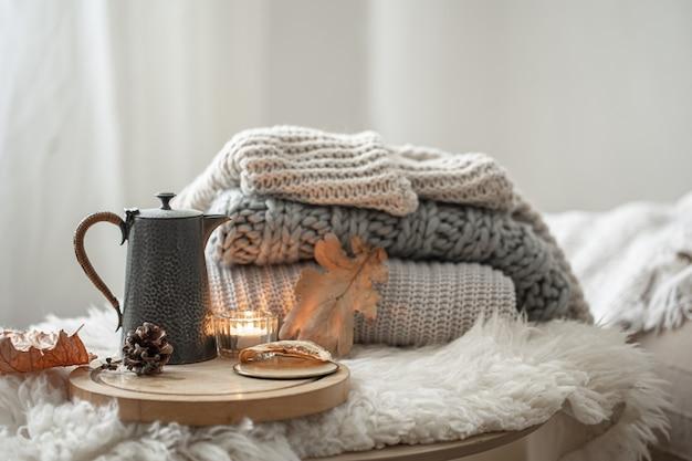 Accueil nature morte avec chandails tricotés et théière de thé sur fond flou.