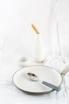 Accueil servant des plats pour manger. assiette vide et cuillère sur la table sur un chiffon blanc. vue verticale