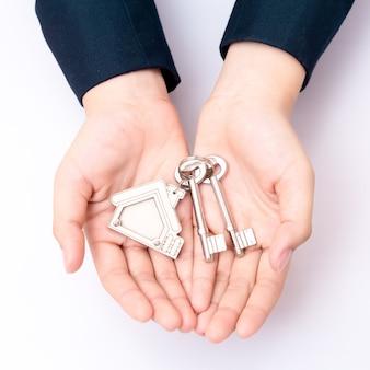 Accueil vendeur tenant la clé de la maison. concept pour les affaires immobilières.