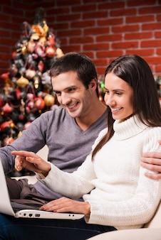 Achat en ligne. beau jeune couple utilisant l'ordinateur ensemble pendant que la femme pointant le moniteur et souriant avec l'arbre de noël en arrière-plan