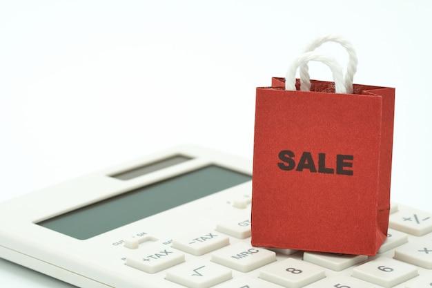 Achat en ligne et service de livraison de sacs à provisions placé sur une calculatrice blanche