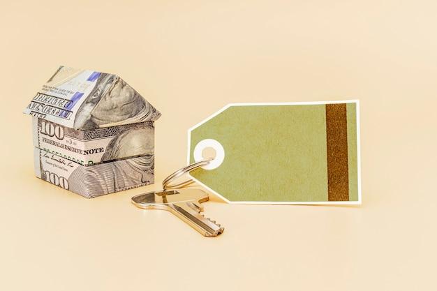 Achat et vente de logements. hypothèque pour l'achat d'une maison. propriété locative. billets de la maison des dollars avec des clés et une étiquette pour le texte. fermer. espace de copie.