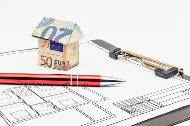 Achat et vente de logements. hypothèque pour l'achat d'une maison. propriété locative. maison faite de billets en euros et d'un stylo à bille sur le projet de la future maison. fermer. espace de copie.