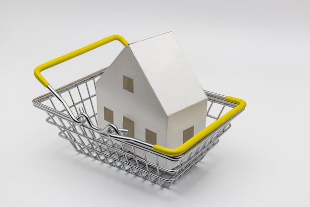 Achat et vente de logements. hypothèque pour l'achat d'une maison. propriété locative. maquette d'une maison en papier dans un caddie d'un magasin. fermer. espace de copie. bonne affaire.