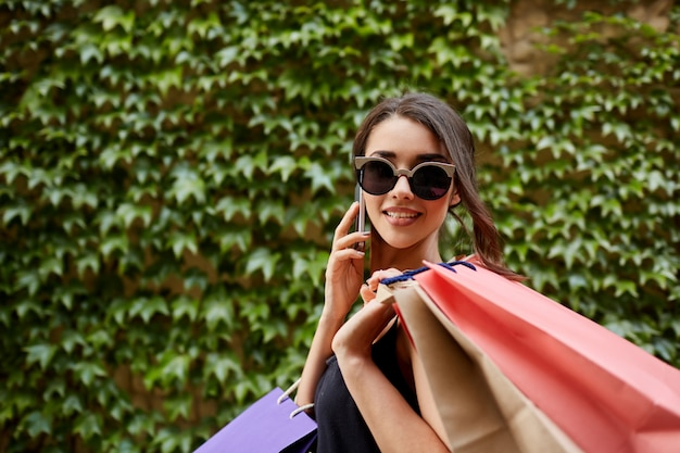 Achats. close up portrait of young attractive tan-skinned caucasian girl in sunglasses and black dress holding lot of bags after shoping, talking on phone with friend, looking in camera with happy a