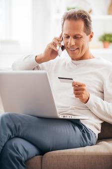 Achats directement de chez vous. cheerful man shopping en ligne alors qu'il était assis sur le canapé à la maison