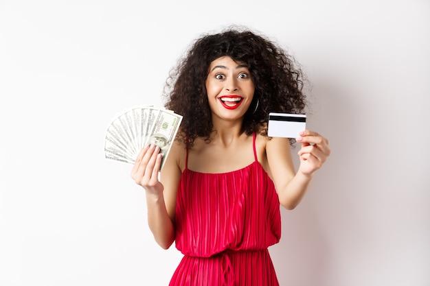 Achats. excité femme aux cheveux bouclés en robe rouge, tenant de l'argent mais montrant une carte de crédit en plastique avec un sourire heureux, fond blanc.