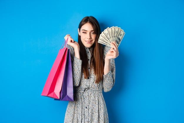Achats. excité jolie femme acheter des cadeaux pour elle-même, montrant des billets d'un dollar et des sacs de couleur de la boutique, souriant satisfait, debout sur le bleu.