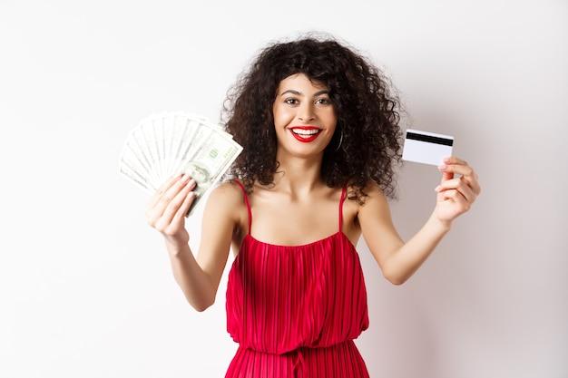 Achats. femme chanceuse en robe élégante, montrant de l'argent et une carte de crédit en plastique, souriant heureux, portant du maquillage, fond blanc.
