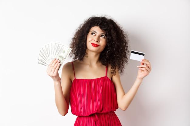 Achats. femme pensant et souriant, tenant de l'argent avec une carte de crédit en plastique, vêtue d'une robe élégante rouge et maquillage de soirée, fond blanc.