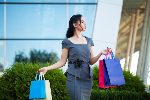Achats. femme tenant des sacs colorés près de son centre commercial en noir vendredi vacances