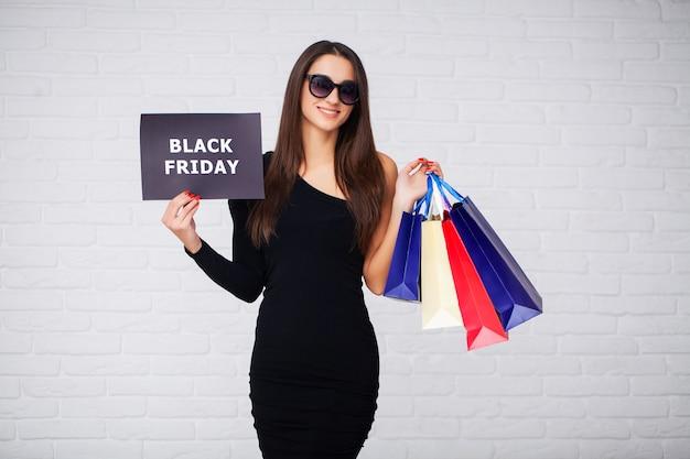Achats. femmes tenant des flans de réduction sur fond blanc en vacances de vendredi noir