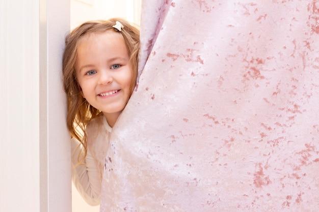 Achats. une fille essaye une belle robe doucement rose dans la cabine d'essayage de la boutique.
