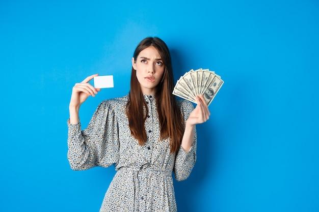 Achats. fille réfléchie regardant et mordant la lèvre, en comptant à l'esprit ou en pensant, tenant une carte de crédit en plastique avec des billets d'un dollar, debout sur le bleu.