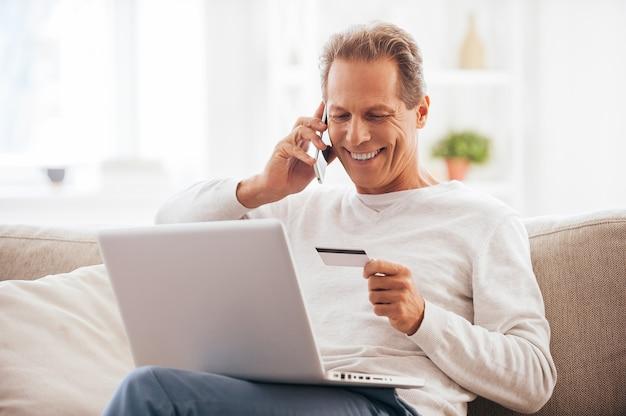 Achats sur internet. cheerful man shopping en ligne alors qu'il était assis sur le canapé à la maison