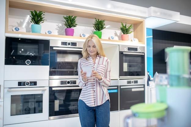 Achats. jolie blonde cliente choisissant des produits dans une salle d'exposition