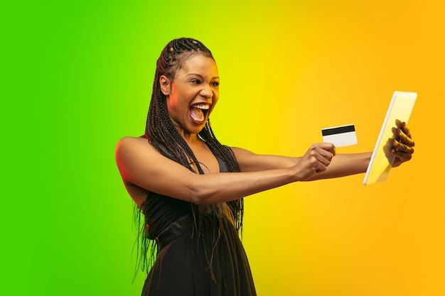 Achats en ligne avec carte et tablette. portrait de jeune femme en néon sur fond dégradé. les émotions humaines, vendredi noir, cyber lundi, achats, ventes, concept financier. couleurs tendance.
