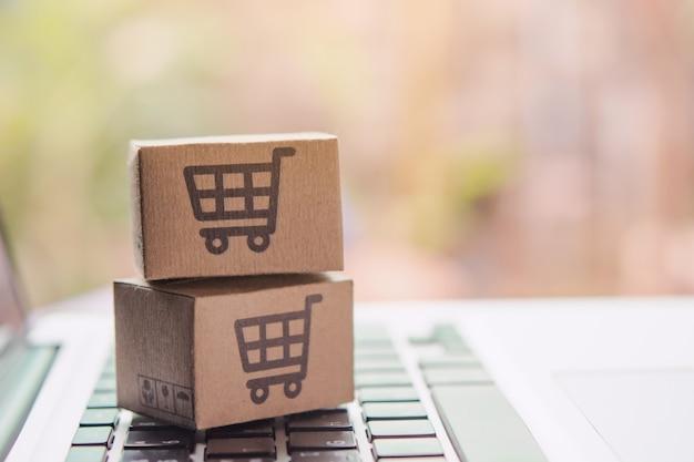 Achats en ligne - cartons ou colis en papier avec un logo de panier sur un clavier d'ordinateur portable. service d'achat sur le web en ligne et offre la livraison à domicile.