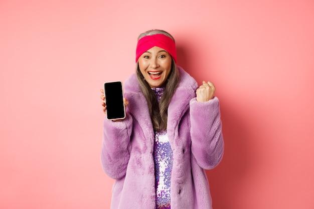 Achats en ligne et concept de mode. heureuse femme âgée asiatique remportant un prix sur internet, montrant un écran de téléphone portable vierge et faisant une pompe à poing, cri de joie, debout sur fond rose.