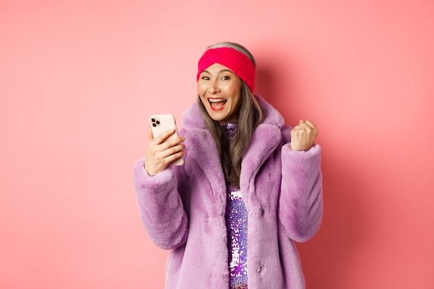 Achats en ligne et concept de mode. heureuse femme senior asiatique remportant un prix sur internet, tenant un téléphone portable et faisant une pompe à poing, cri de joie, debout sur fond rose.