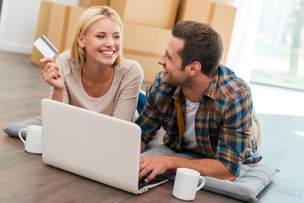 Les achats en ligne facilitent la vie. jeune couple souriant allongé sur le sol de leur nouvel appartement et faisant des achats sur internet tandis que des boîtes en carton sont posées en arrière-plan