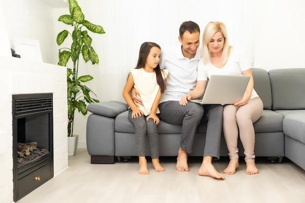 Achats en ligne en famille. famille heureuse souriante assise sur le canapé et faisant des achats en ligne ensemble
