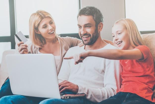 Achats en ligne en famille. famille heureuse de trois personnes se liant les unes aux autres et souriantes assises sur le canapé et faisant des achats en ligne ensemble