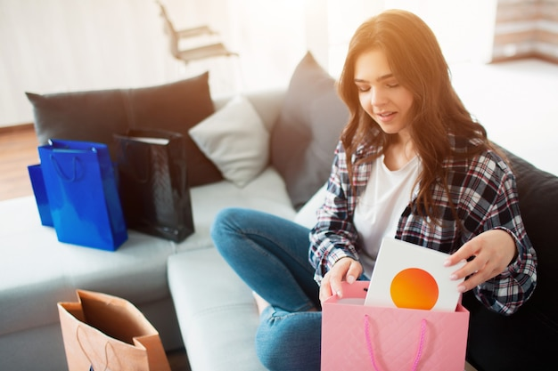 Achats en ligne, une jeune femme a commandé une livraison à domicile. maintenant, elle s'assoit sur le canapé et déballe ses nouveaux achats.