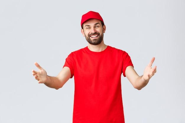 Achats en ligne, livraison pendant la quarantaine et concept de plats à emporter. coursier sympathique et agréable en t-shirt rouge et casquette, uniforme de l'entreprise, tendant les mains vers le client ou la commande, prenant le colis