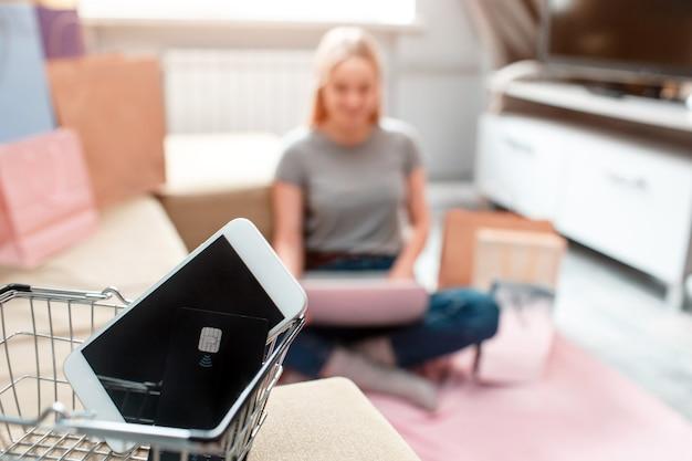 Achats en ligne à la maison. la carte de crédit et le smartphone noirs sont prêts pour la vente du vendredi noir sur fond d'acheteur avec ordinateur portable