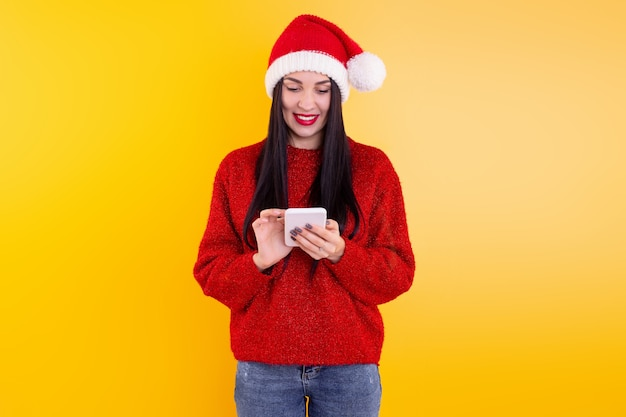 Achats en ligne de noël. l'acheteur féminin passe la commande à l'écran du smartphone avec espace de copie. une femme achète des cadeaux pour la veille de noël. soldes vacances d'hiver