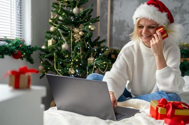 Achats en ligne de noël. l'acheteur fille passe commande sur ordinateur portable. une femme achète des cadeaux, se prépare à noël, parmi les coffrets cadeaux et les paquets. ventes de vacances d'hiver.